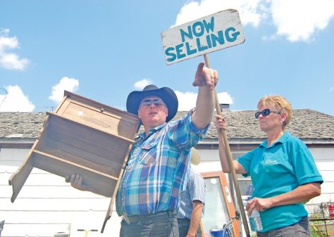 Glen Manz points to a bidder as a small wooden cabinet goes up for sale during the Burgess auction in Bladworth on June 6. Also pictured is Connie Glines.