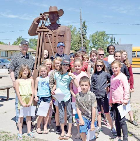 Don Wilkins poses for a photo with a group of students at the surveyor statue in Chamberlain.