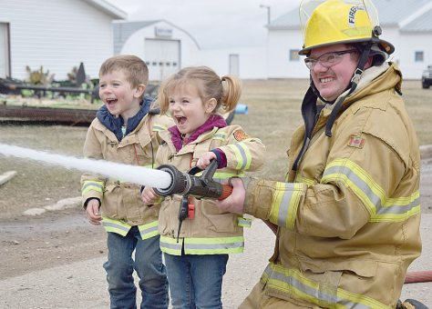Davin McNabb, 4, and his sister Jayla, 2, had a blast trying out the fire hose during the Davidson Volunteer Fire Department's open house on April 22. Helping them out is firefighter Tim Bruch.