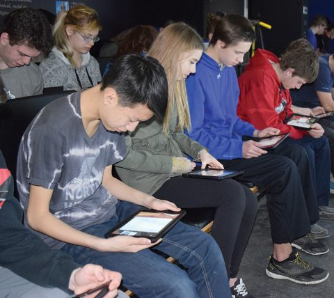 From left, Davidson students Andrew Lee, Breanne Townsend, Phoenix Prpick and Keegan Shaw use tablets to work through an activity while on the Holodomor Mobile Classroom on April 24.