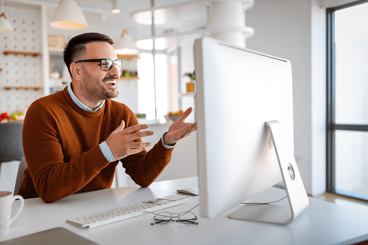 A man smiles while talking to his online leadership coach.