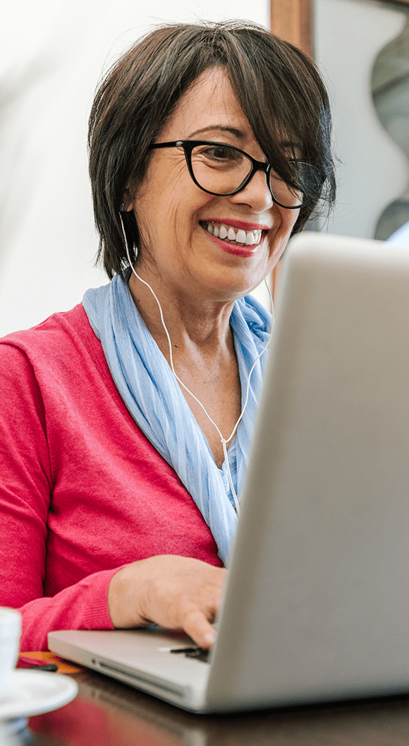 A professional woman smiles while taking an online leadership training class.