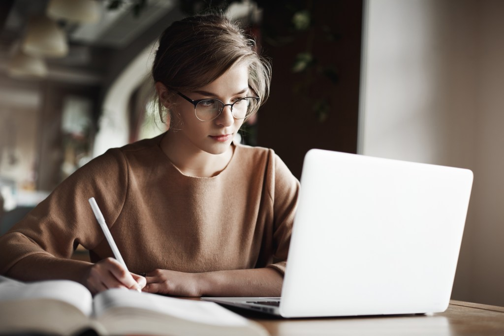 Creative good-looking european female with fair hair in trendy glasses, making notes while looking at laptop screen, working or preparing for business meeting, being focused and hardworking