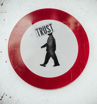 Street sign of the word trust with a red circle around it