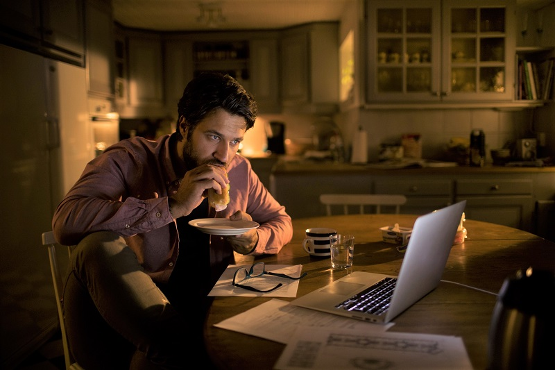 Man eating a late-night meal in front of laptop before sleep