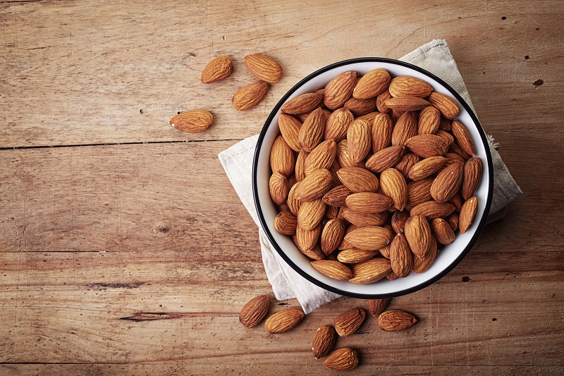 Bowl of whole almonds set on a table.