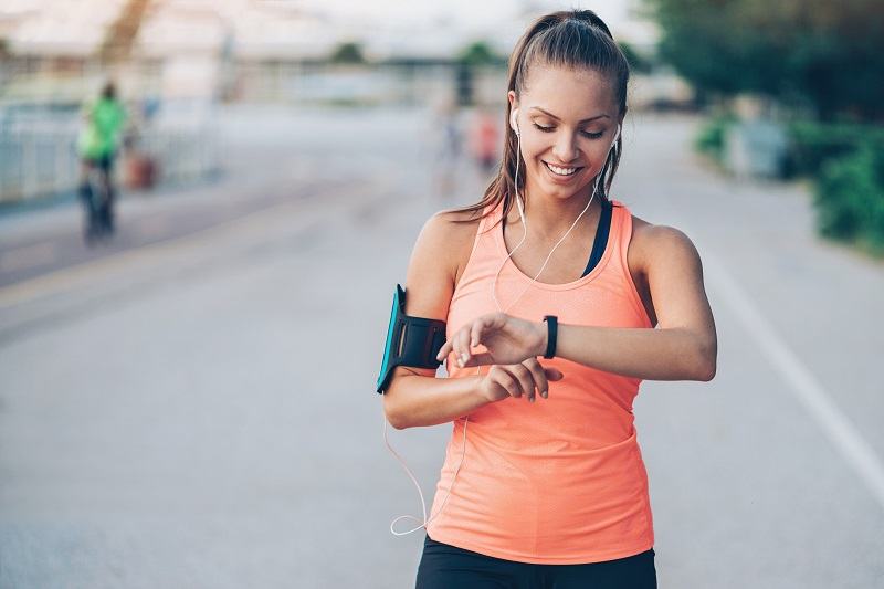 woman in running gear and headphones checking her watch. pear shaped body fat loss