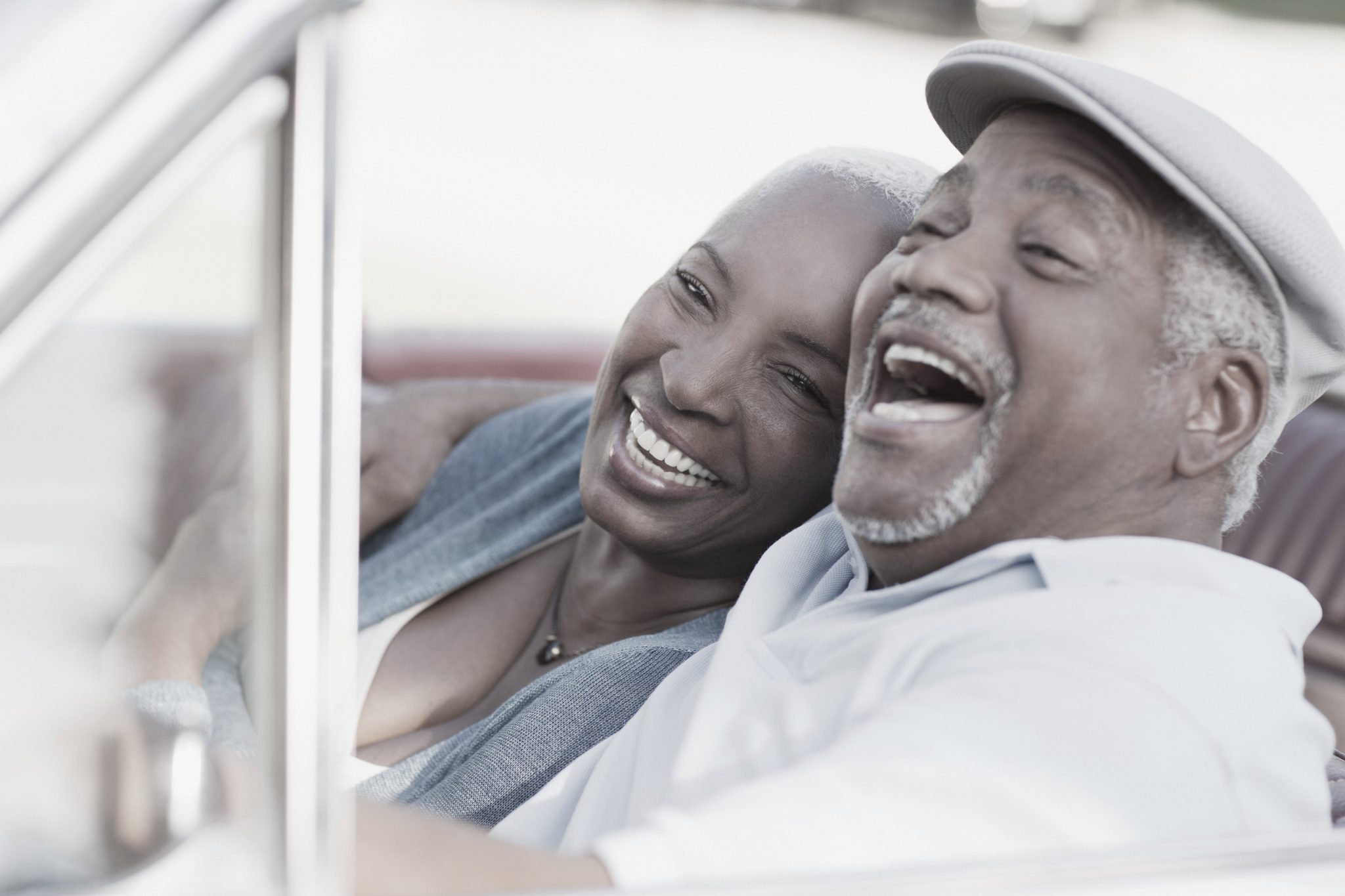 Smiling couple laughing in car