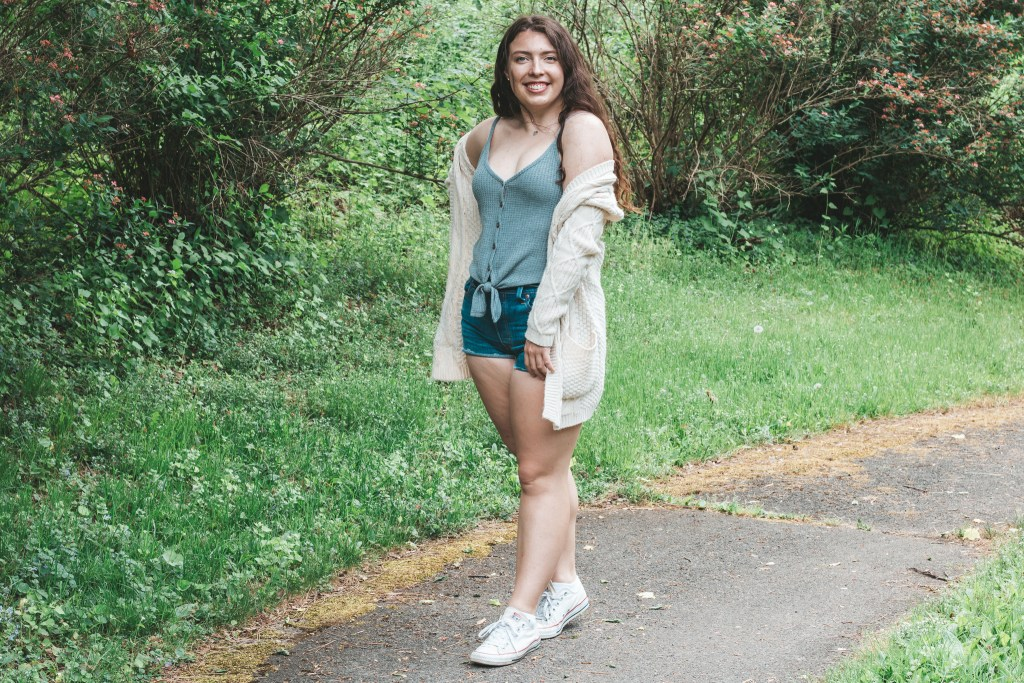 Model posing on a bike path in a cream cardigan, tied grey tank top, denim cut off jeans and white converse sneakers