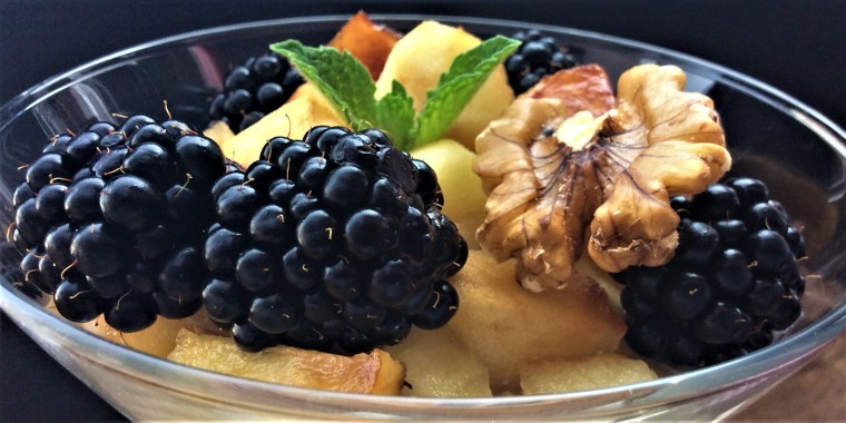 Overnight oats with cinnamon apples, blackberries, walnuts and mint