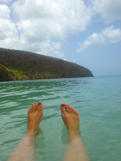 A pair of tanned feet floating in the blue-green waters of the Caribbean.