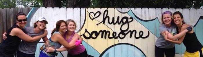 "Women runners hug in front of graffiti that says ""Hug Someone."""