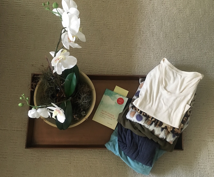 Photo of orchid and folded clothes on tray with Marie Kondo book on tidying up.