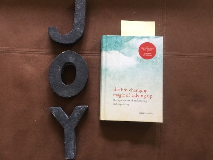 Photo of letters spelling out JOY and Marie Kondo book on tidying up.