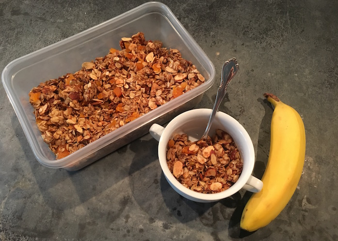Homemade apricot granola in bin and bowl with banana