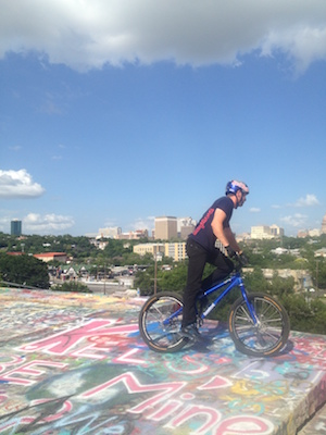 Danny MacAskill on his bike, preparing to drop down Austin's Baylor Street Art Wall, in 2014