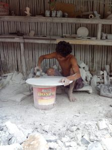 A young man working on a marble table.