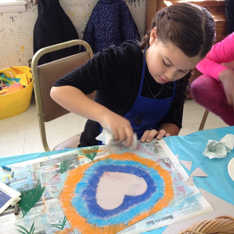 young girl makes a painting with watercolor