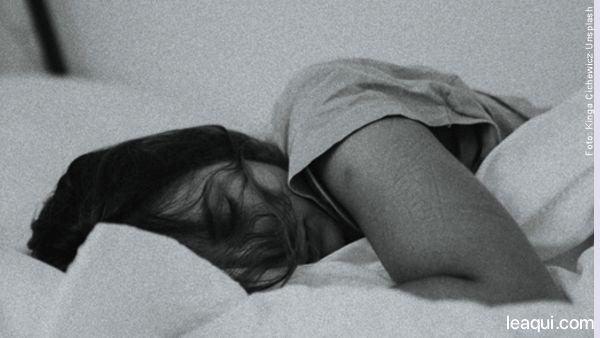 Mulher deitada dormindo em meio a lençóis: desperte a sua energia e comece um novo dia