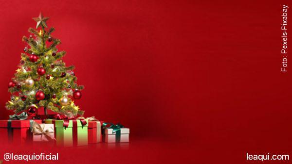 Uma arvore de natal com presentes à sua volta em um fundo vermelho representando o significado do natal