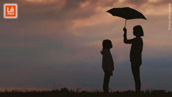pessoa com guarda-chuva protegendo criança demonstrando melhor forma de ajudar alguém