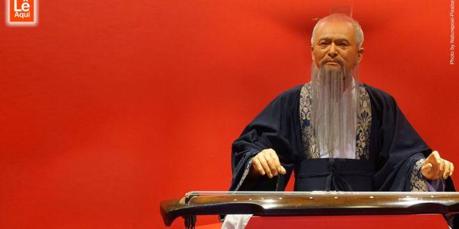 Estátua de cera de Confúcio tendo o fundo vermelho