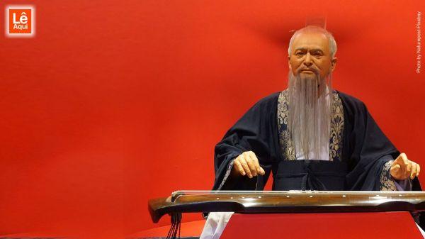 Estátua de cera de Confúcio tendo o fundo vermelho, indicando frases de Confúcio