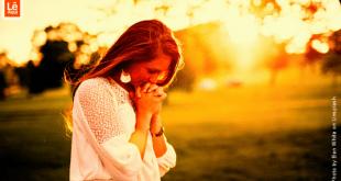 Mulher em postura de agradecimento emanando energia da gratidão