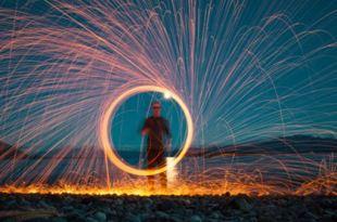 Homem no centro de uma roda de faíscas que se espalham para todas as direções numa tentativa de mudar o carma