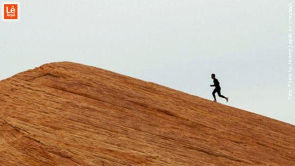 Homem correndo subindo uma montanha buscando realizar seus objetivos