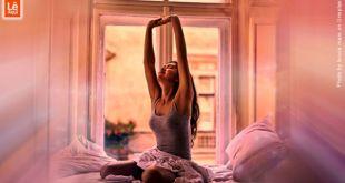 Mulher se espreguiçando ao se levantar da cama expressando deus primeiros pensamentos