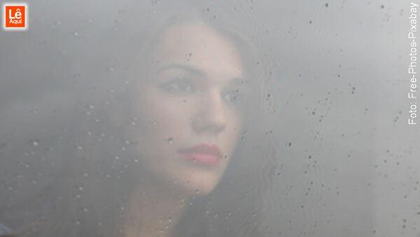 Mulher com olhar triste olhando por uma janela respingada de chuva denotando que a mente está cinzenta