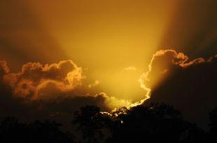 Nascer do sol com a dourada luz vencendo as densas nuvens afirmando o poder da fé s