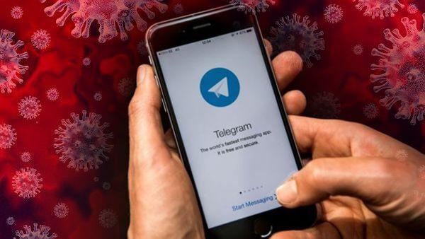 mãos segurando telefone celular com o aplicativo Telegram sobre coronavírus