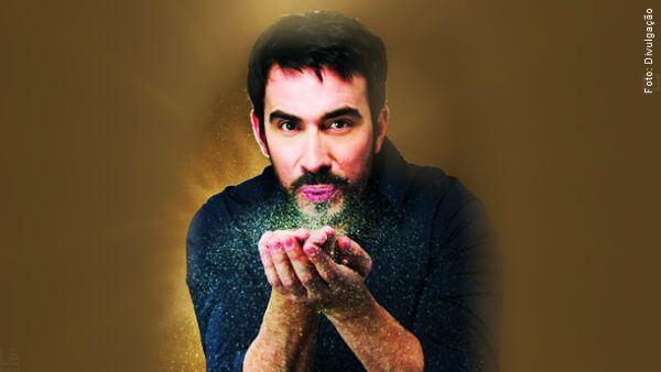 Padre Fábio de Melo com as mãos em concha soprando brilhos luminosos espalhando coragem e fé