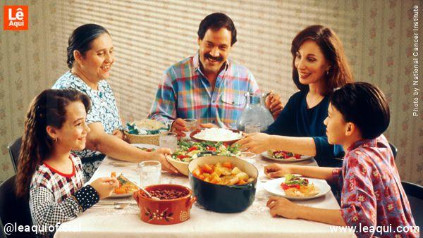 família com pai, mãe, casal de filhos e uma senhora na mesa jantando para superar dificuldades de convívio quarentena