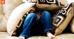 Menino sentado em um sofá se escondendo em meio a almofadas amor medo