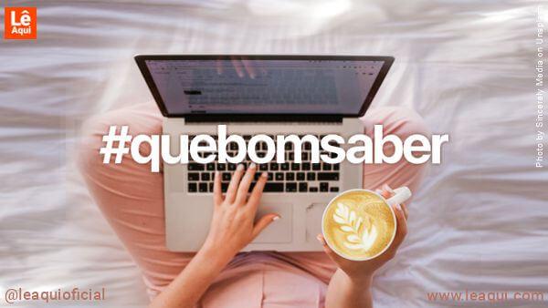 Mulher segurando uma xícara de café e um computados no colo está lendo Que Bom Saber - nº4