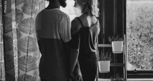 Casal em uma sala olhando pela janela amor pandemia