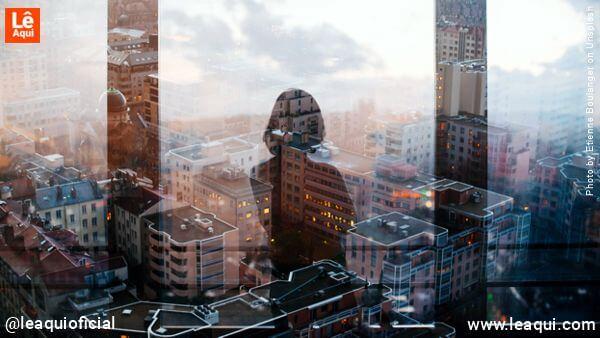 imagem de uma mulher refletida em uma janela que mostra uma grande metrópole indicando necessidade de aliviar a solidão