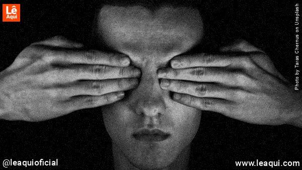 rosto de homem tapando os olhos com suas mãos simbolizando a negação da realidade
