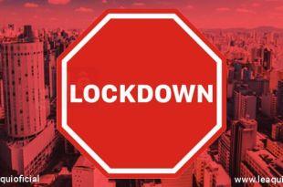 placa vermelha com a inscrição de lockdown sobrepondo-se à fotografia do centro da cidade de são paulo
