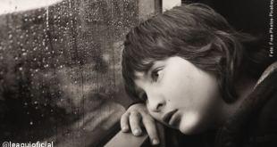 criança olhando tristemente por uma janela demonstrando estresse emocional pandemia