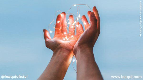 duas mãos com luzes louvando verdadeiro amor