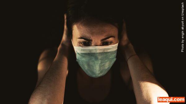 mulher usando máscara ati coronavírus com as mãos na cabeça demonstrando ansiedade e medo epidemia silenciosa