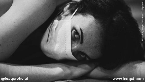 mulher deitada com máscara cirúrgica Emoções pandemia