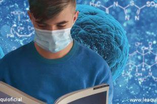 Jovem rapaz com máscara cirurgica lendo um livro escolar tendo ao fundo ilustração do coronavírus pandemia adolescentes