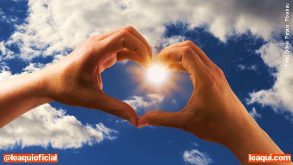 mãos unidas formando um coração tendo no centro o sol em céu azul vazio no peito