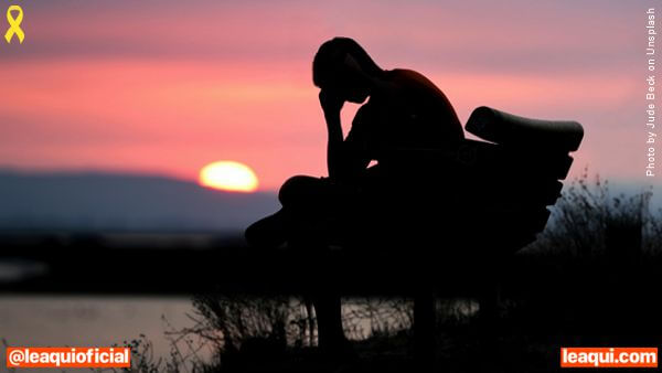 Homem sentado em um banco de praça apoiando a cabeça com o sol se pondo ao fundo saúde mental na pandemia