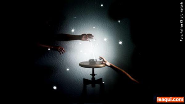 um foco de luz no centro revelando uma pequena mesa redonda com uma ampulheta sob ela e mãos de um lado e de outro viver no presente